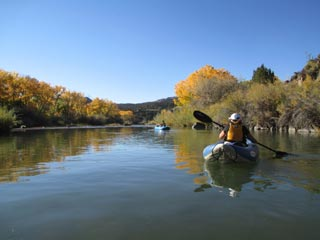 kayak on calm river with golden-leaved trees behind and mountain in the distance