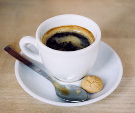 Awhite cup of dark coffer with a ring of crema; in the saucer sit a small spoon and a tea cookie