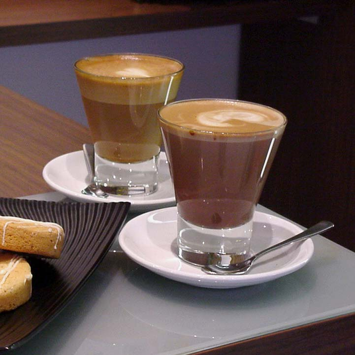 A table with grey placemat holds two white saucers, each containing a glass filled with coffee. In the front saucer rests a small, silver spoon. To the left, dark brown plate with biscotti rests.