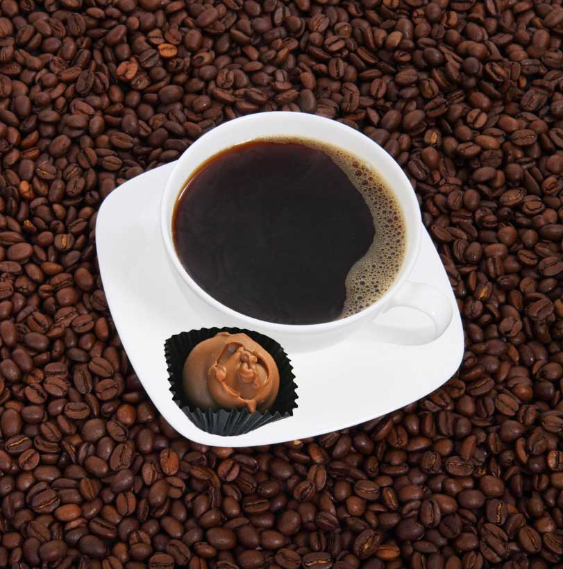 A white cup, filled with black coffee, sits in a matching saucer atopa field of roasted coffee beans; in the saucer rests a chocolate truffle candy.