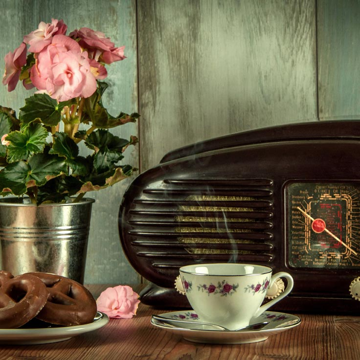 On a wooden table sit apotted miniature pink rose, a vintage radio and a china coffee cup.