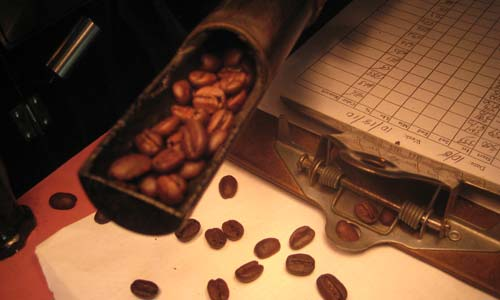coffee beans in a trowel held above a few scattered beans on a paper beneath a bright light