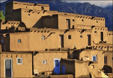 three-story pueblo with mountain in background