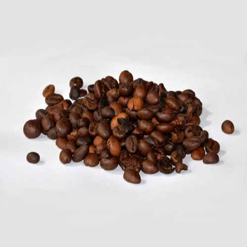 A small pile of roasted coffee beans of varied sizes and brown tones