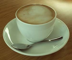 A white cup of coffee with froth--crema--sits atop a white saucer; a small silver spoon rests in the saucer
