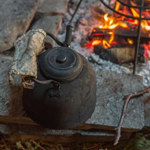 An iron kettle sits beside a campfire