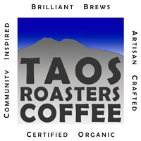 Grey mountain silhouette against a bright blue sky; over mountain in imposed Taos Roasters Coffee; around image in white border reads Community Inspired, Brilliant Brews, Artisan Crafted, Certified Organic