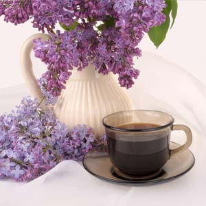 White vase filled with lilacs sits behind a brown cup of coffee, sitting in a saucer